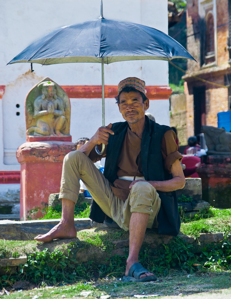 The Umbrella Man . To shade himself from scorching sun of Kathmandu a man poses with an umbrella.