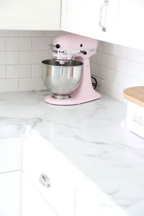 Gorgeous kitchen with white cabinetry accented with nickel hardware and 180X Formica with Amore Edge counters below a white subway tile backsplash which frames a pink KitchenAid Mixer tucked into the corner.