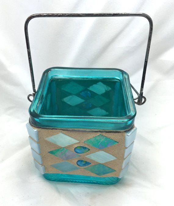 3 sostenedor de vela de mosaico cuadrado con mango metálico. Esta delicada pieza se encuentra en un marco de cristal azul aqua con una manija del metal. Las teselas son en tonos de azul pálido, perlado, azul agua y blanco. Perlas de vidrio de gota de lágrima que adornan cada lado. El artículo viene con una vela votiva blanca y refleja la luz maravillosamente.