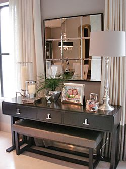 When styling a console table I love to place a bench below if space allows.  When you do place a mirror over a console break it up with some framed family pictures, a lamp and some small greenery to make it feel finished!   Don 't be afraid to add texture with some drapes falling behind the walls next to the windows!