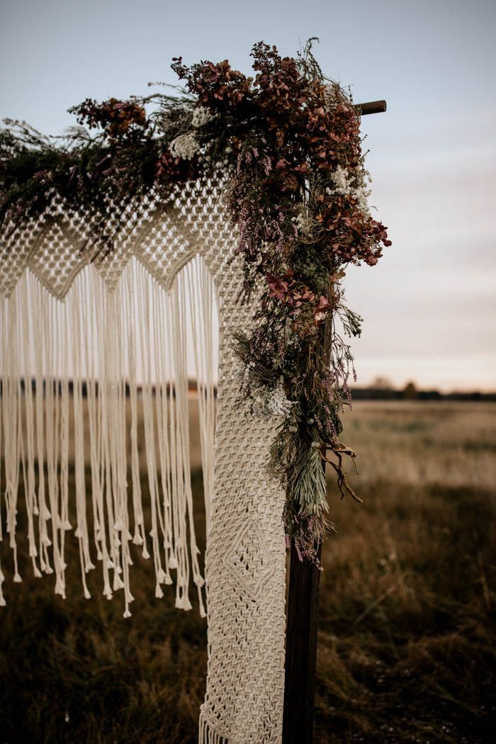 Macrame + moody floral ceremony arch | Image by Chris and Ruth Photography
