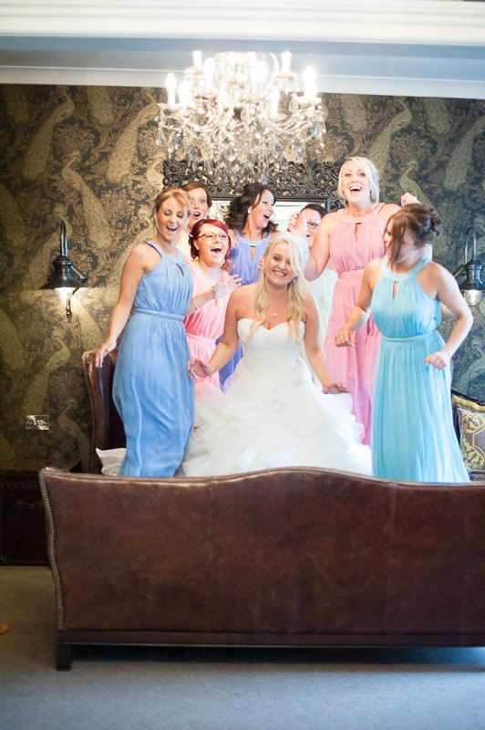 The #bride and her #bridesmaids have a mad moment bouncing on the bed in the bridal suit in EavesHall, Clitheroe.