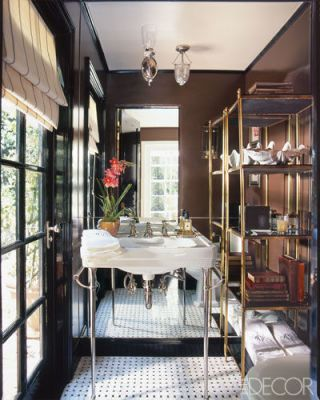 A mirrored wall and a brass-and-marble étagère add an urbane touch to the powder room of Mike Clifford's 1930s Tudor house in Los Angeles. The washstand is by Waterworks, and the walls are painted in Fine Paints of Europe's Dutch Chocolate.