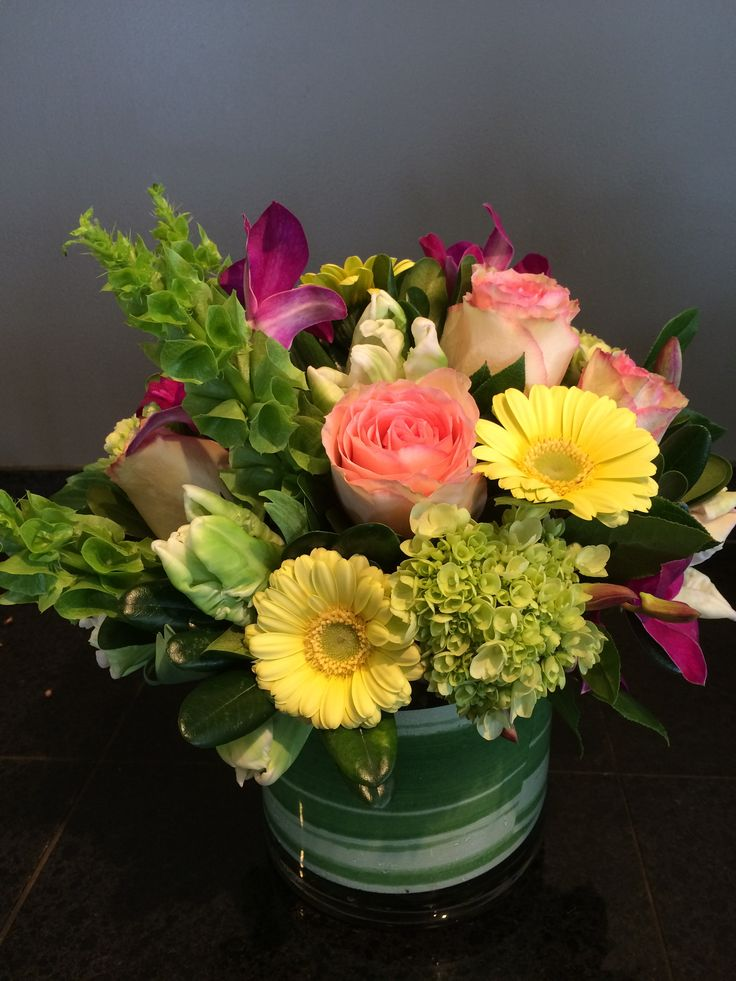 Bells of Ireland, esperance roses, mini-gerbera daisies, mini green hydrangeas, purple dendrobium orchids, with our signature leaf wrap inside a clear cylinder vase