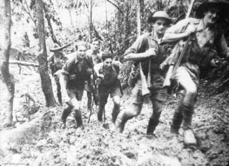 Young Militia soldiers of the 39th Battalion returning to back down the Kokoda Track to their base camp after a battle at Isurava. Their shoes sink deep in the ozzing mud on the hilly jungle track.