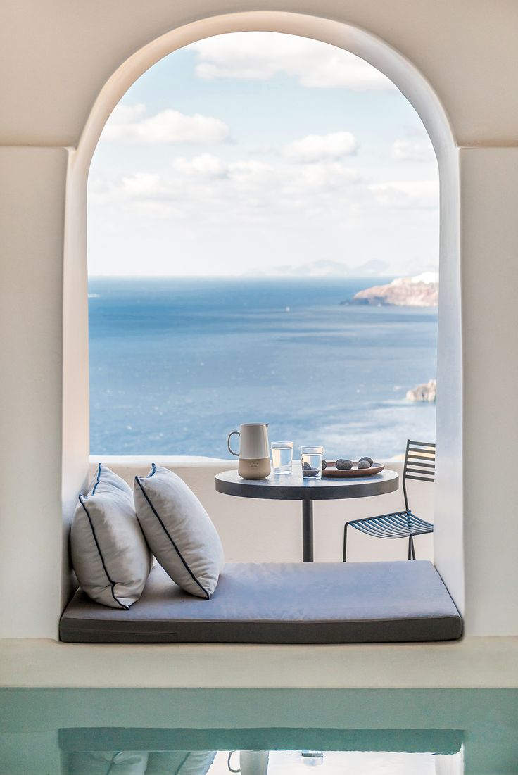 Beautiful views out across the sea framed by a seated archway - aboratorium renovate seven suites at Porto Fira luxury hotel in Santorini, Greece. Luxury hotel designs feature on the www.martynwhitedesigns.com interior design blog.