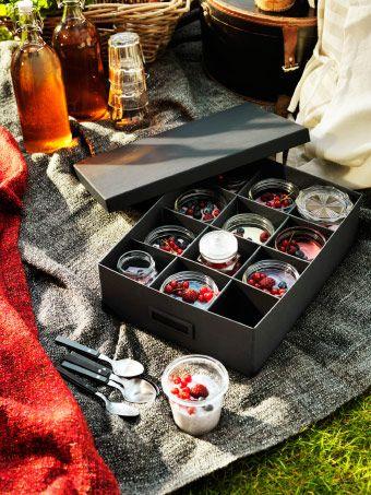 TJENA Kasten mit Fächern in Schwarz gefüllt mit Jogurtgläsern und Obst auf einem Picknicktuch