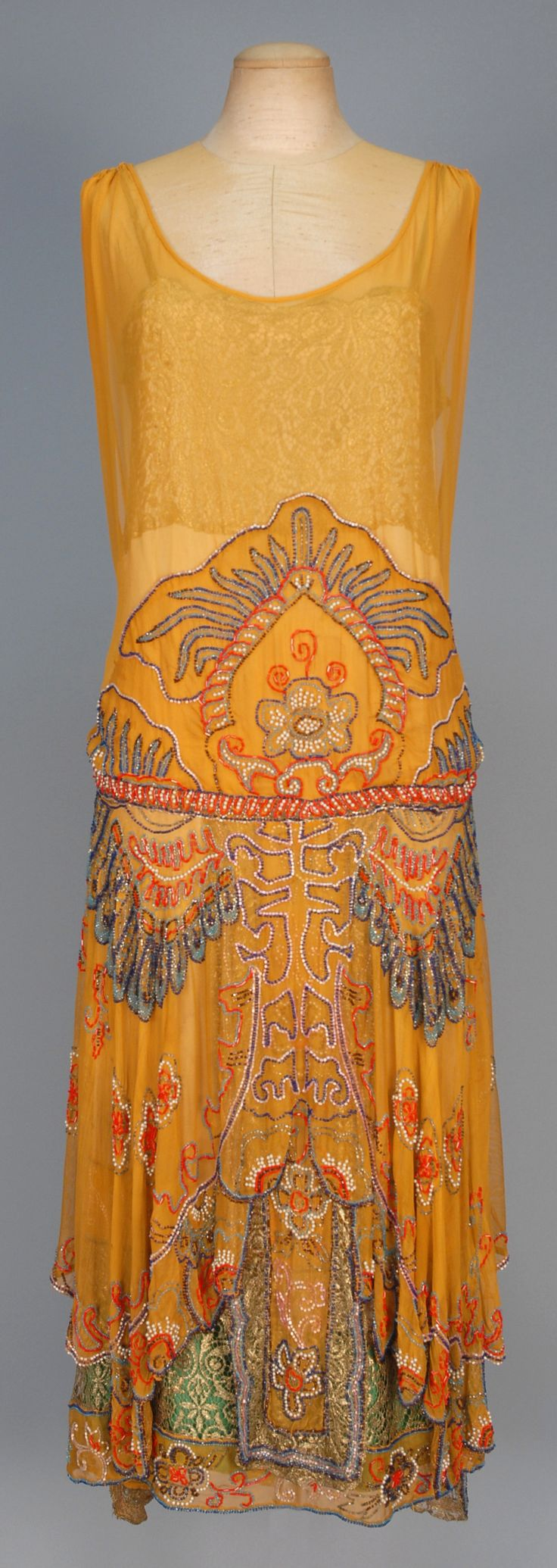 BEADED CHIFFON DINNER DRESS with METALLIC LACE, 1920s. Sleeveless pumpkin silk decorated with elaborate polychrome beadwork and pearls, scalloped and lobed front hem with back streamers revealing satin under-dress with beaded and metallic lace hem and lace bodice top. B-36, L-46. (Tiny hole in skirt and under-dress, few tiny faint spots, very minor bead loss) excellent.