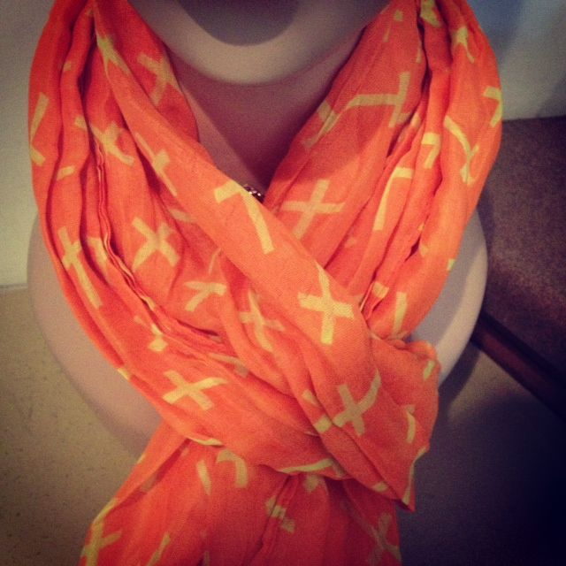 This bright orange scarf is dotted with tiny yellow crosses! Get it for only $12. Available at www.facebook.com/... or call 815-777-3553 to place an order.