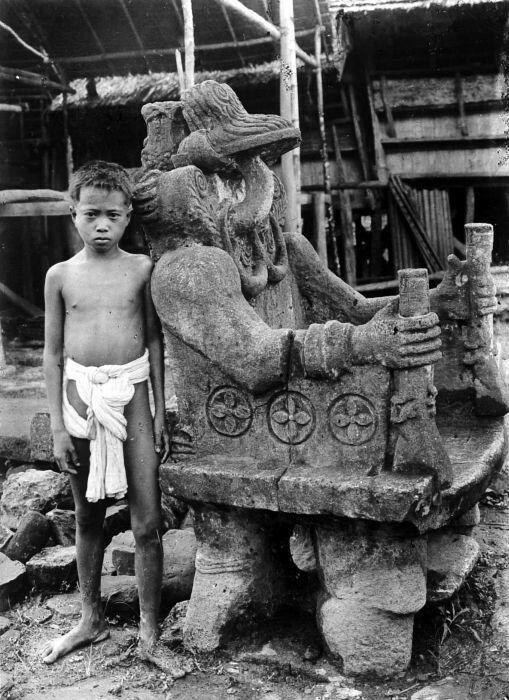 Jongetje naast de stenen zetel van het dorpshoofd van het dorp Hilisimetano  Nias - Unknown date