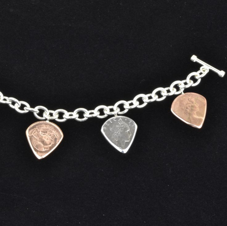 Prices start at $176 for a 100% sterling silver charm bracelet and one pick, and go up depending on number of picks ($39.95 - $59.95 each) and type of bracelet (silver, yellow gold, white gold). The one shown is$295 for 100% sterling silver charm bracelet with4 picks.  Each international coin is handcrafted into a guitar pick shape and attached to a 100% sterling silver bracelet with bail. Guitar picks from coins are used by professional musicians like Brian May from Queen and Billy…