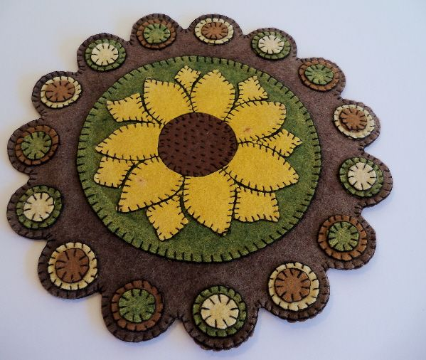 """A great felt mat with appliqued """"pennies"""" and a large central sunflower. The mat which was found in Maine, is in excellent condition with expected wear to the backing. The creator of this mat made an excellent choice of colors and design both of which are enhanced by the scalloped edge. This mat was sewn around 1920-1930. 12"""" diameter.  $250."""