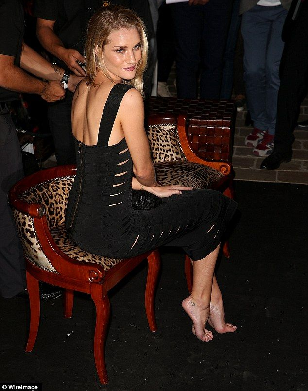 Looking good: Rosie Huntington-Whiteley slipped into a skintight black dress that featured cut-outs on the side as she sat barefoot at the p...