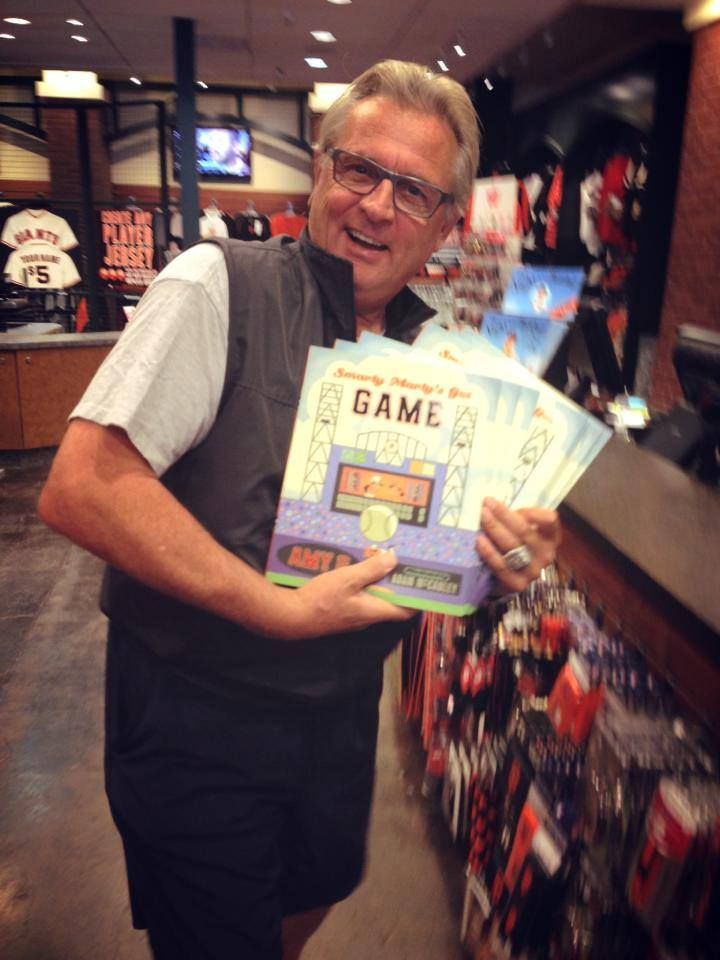 """Giants broadcaster DUANE KUIPER in the Giants Dugout store picking up copies of """"Smarty Marty's Got Game"""", a children's book by Amy Gutierrez (Author) and Adam McCauley (Illustrator)."""
