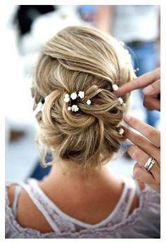 A few flowers give this updo the final touch | Unas flores adornan este precioso peinado recogido de novia