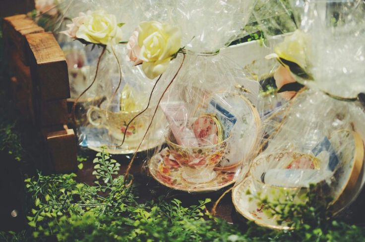 Garden themed bridesmaid gifts, with vintage odd teacups filled with floral hand cream a floral compact mirror, floral tea bag, wrapped in cellophane and roses