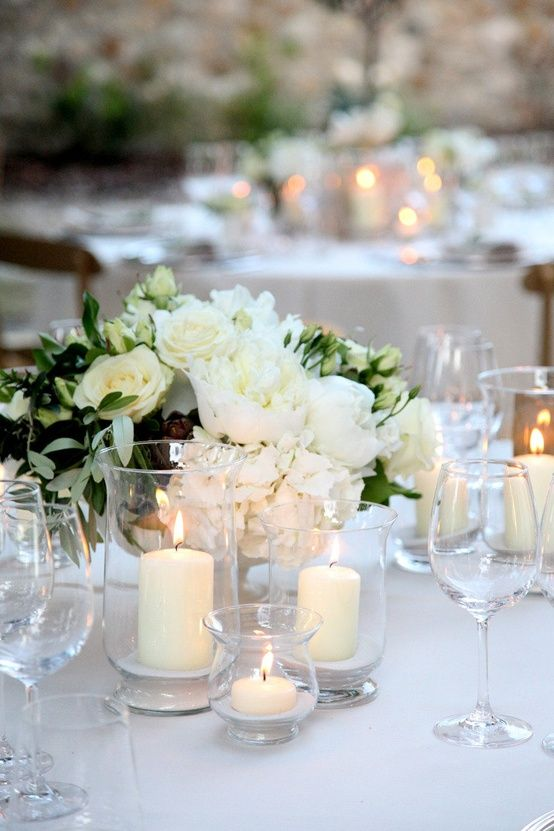 Other tables will have a low silver vintage compote vase spilling with green seeded eucalyptus, cream hydrangeas, pale peachy-pink spray roses, queen anne's lace, peach stock flowers, and grey dusty miller surrounded by tall fluted votives and low fluted votives.