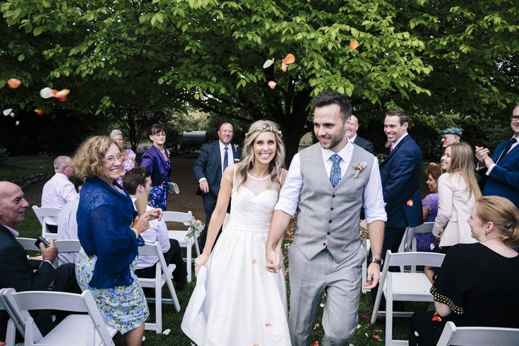Wedding ceremony throwing confetti as bride and groom walk down the aisle at Poachers Pantry, NSW