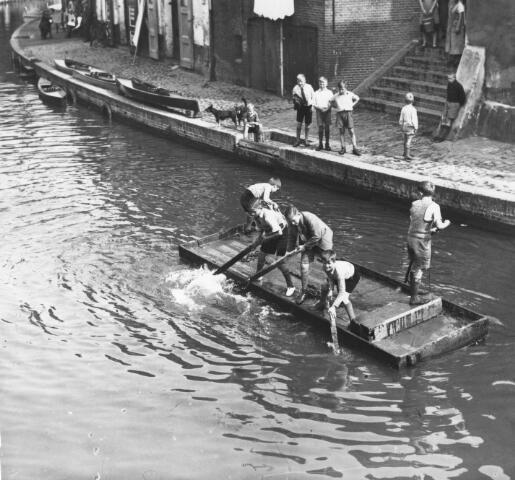 Jongens op een vlot in de Oudegracht te Utrecht, met op de achtergrond de Twijnstraat aan de Werf. Catalogusnummer 350410