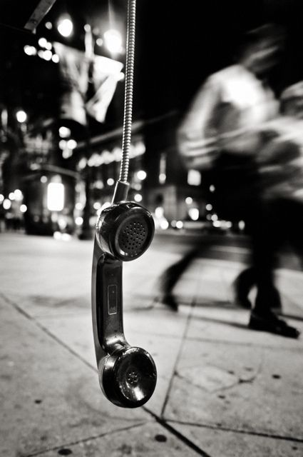 This is a great image because of the contrast between the dangling phone and the blurred people in the background.