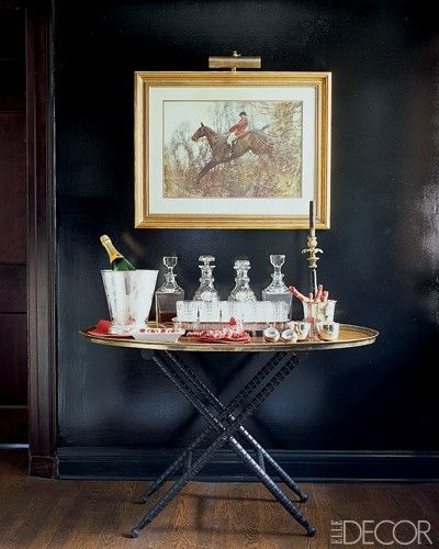 Bar, black walls, equestrian painting framed in gold - in the Kentucky home of Mark Badgley and James Mischka