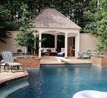 This cabana, with its solid roof, has both an open-air and a sheltered feel. The structure houses a bath and changing rooms, a snack bar,gas grill,refrigerator, and a cozy seating area. An old jukebox inside provides water music.