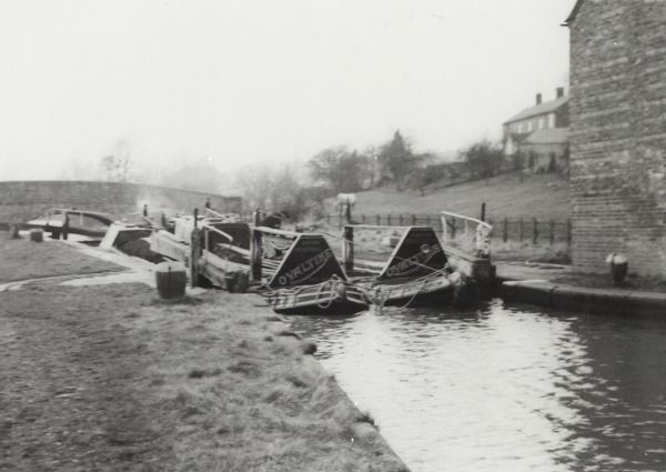 BW192-3-2-2-13-1-313 Pair of Ovaltine narrowboats at Braunston lock flight on the Grand Union Canal Description Black and white photograph taken from beside the canal, shows the boats breasted up entering a lock,