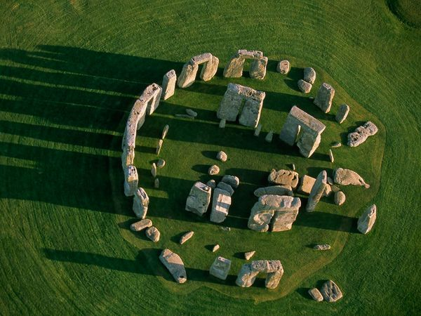 At ground level, the ruins of Stonehenge appear somewhat random and chaotic, but a view from the air reveals the monument's circular order. The site started out modestly around 3100 B.C. as a wide ring of wood posts surrounded by a ditch and bank. The familiar enormous rock slabs, some brought from hundreds of miles away, were added to the interior over a period of about 1,500 years.