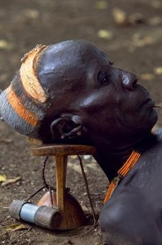 Africa | An elder of the Karo tribe rests with his head on his wooden head-rest which protects his elaborate clay hairdo. Every man carries a headrest which doubles as a stool. This man has attached his snuff box to it. Duss, Omo Valley, Ethiopia | ©John Warburton-Lee