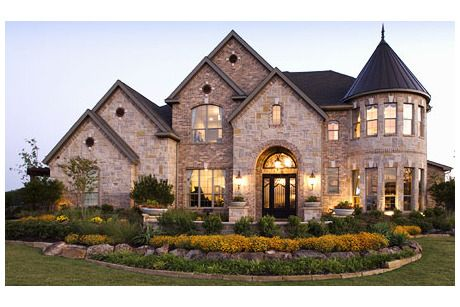 A rounded, two-story turret with closely spaced windows adds rich character to this brick and stone new home