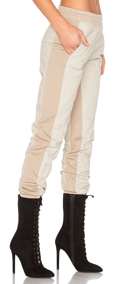 Tyvek jogger pant by YEEZY Season 3. Self: 100% polypropyleneContrast: 98% poly 2% lycra. Elasticized waistband. Ribbed side panels. Elasticized cuffs. YE...