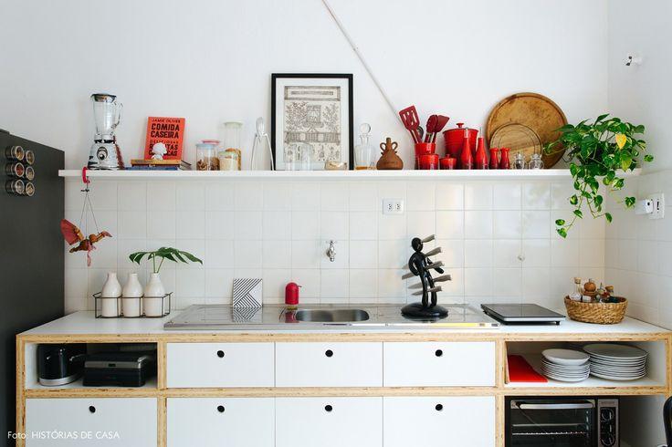 Cozinha tem revestimento de azulejo branco e marcenaria feita com compensado e revestida com fórmica branca.