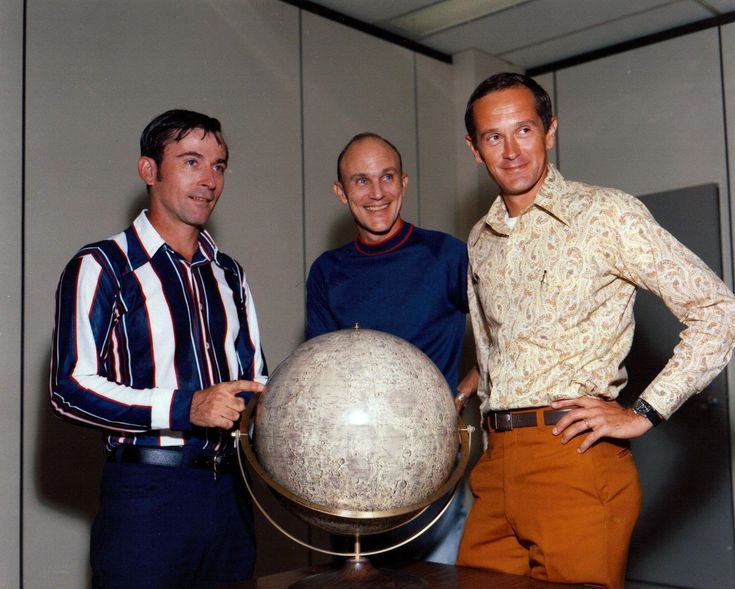 Apollo 16 John Young (left), Ken Mattingly, and Charlie Duke pose for an informal picture with a lunar globe. John is not pointing at the landing site.