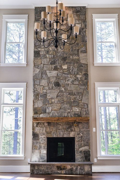 Family Room: Two story stone fireplace, rustic wood mantle, flanked by windows, dark hardwood floors, neutral color paint. Just needs built-ins where the the bottom windows are. :)
