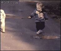 Cute kid walking dog stops to play in the puddle