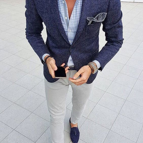 This combination of a navy wool coat and grey chinos is perfect for a night out or smart-casual occasions. Channel your inner Ryan Gosling and choose a pair of dark blue suede tassel loafers to class up your look.   Shop this look on Lookastic: https://lookastic.com/men/looks/blazer-long-sleeve-shirt-chinos/21089   — Light Blue Gingham Long Sleeve Shirt  — Navy Polka Dot Pocket Square  — Navy Wool Blazer  — Grey Chinos  — Navy Suede Tassel Loafers