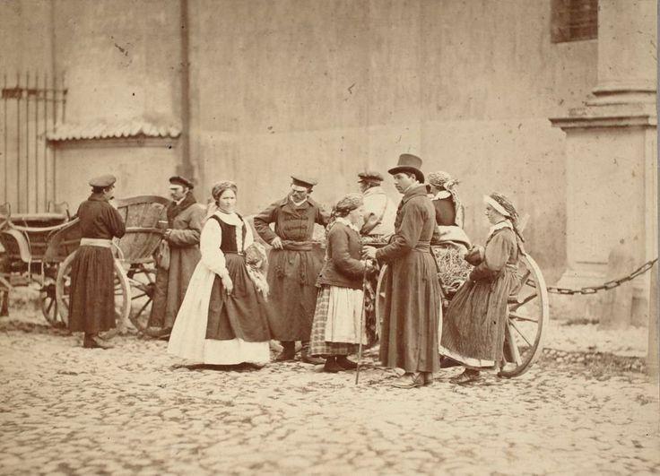 Grupa wieśniaków z Wilanowa przy kościele Wizytek. W 1866 roku Karol Beyer skierował swój obiektyw ku środowisku podwarszawskich chłopów zamieszkujących Wilanów, Miedzeszyn i Kawęczyn. Fotografie 'włościan z Powiatu warszawskiego, w ich stronach, przy narzędziach do pracy rolnej lub gospodarskiej służących' planował wysłać na wystawę etnograficzną w Moskwie. Zdjęcie pochodzi z 1866 r.