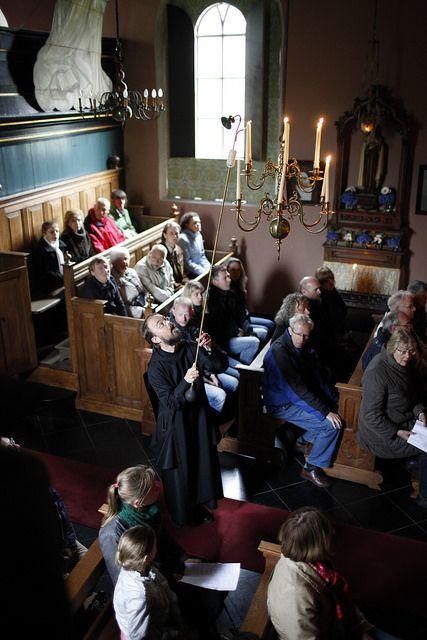 Broeder Hugo ontsteekt de kroonluchter in het schip van het heiligdom in Warfhuizen