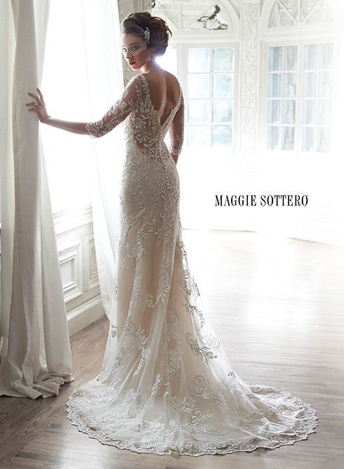A dramatic illusion lace back adorns this hand-embellished sheath gown glimmering with metallic lace appliqués, and embroidered with Swarovski crystals, drifting from shoulder to floor-skimming hem. A delicate scalloped hemline finishes the look... Verina by Maggie Sottero.