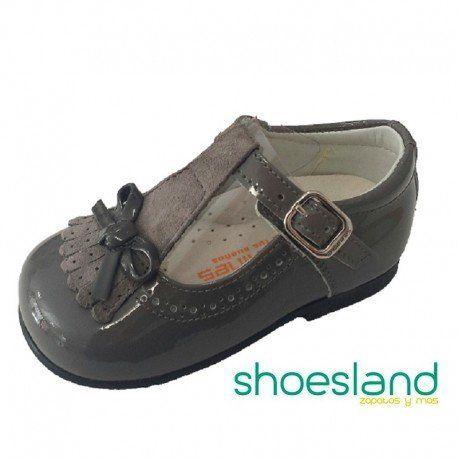 Zapatos tipo merceditas para niña de Andanines en un elegante y combinable charol color gris ceniza cerrado con hebilla para sujetar bien el pie en sus primeros pasos  Desde el 18 hasta el 24