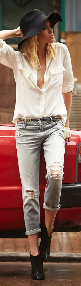 Flowy pale blouse with distressed grey jeans, a studded skinny belt, black leather booties, and a dark floppy hat
