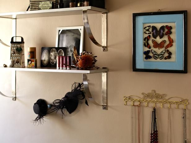 Teenage Girl's Goth-Style Bathroom: Just because shelving is practical doesn't mean it can't be pretty. These curved, chromed brackets give these shelves a feminine quality. Mixing her products with pictures creates interest and storage.  From DIYnetwork.com