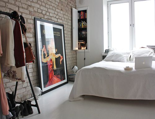 exposed brick wall, old french film posters, all white sheets, lots of natural light... i love this!