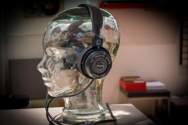 """Grado baut in Brooklyn seit etwa 60 Jahren Kopfhörer und Tonabnehmer. Die Kopfhörer erinnern an die Modelle, die man als Funker im Korea-Krieg benutzte, obwohl letztere sich kaum für Musikwiedergabe eigneten. Der zur Prestige-Serie zugehörige SR225e ist ein offener, dynamischer Kopfhörer der Gattung """"on-ear"""" und geht je nach Grösse der Ohren schon fast in Richtung """"over-ear""""."""