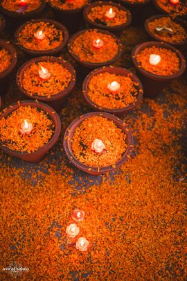 Mehendi Decor - Marigold Floral Decor   WedMeGood An extremely Indian theme inspired Decor, with diyas and genda phool with floating candles for the mehendi. #wedmegood #genda #marigold #diya