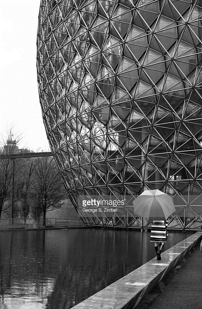 A woman with an umbrella walks along the water pool adjacent to the Montreal Biosphere during Expo '67 (or 1967 International and Universal Exposition), Montreal, Quebec, Canada, 1967. The sphere was constructed in the manner of Buckminster Fuller's geodesic domes.