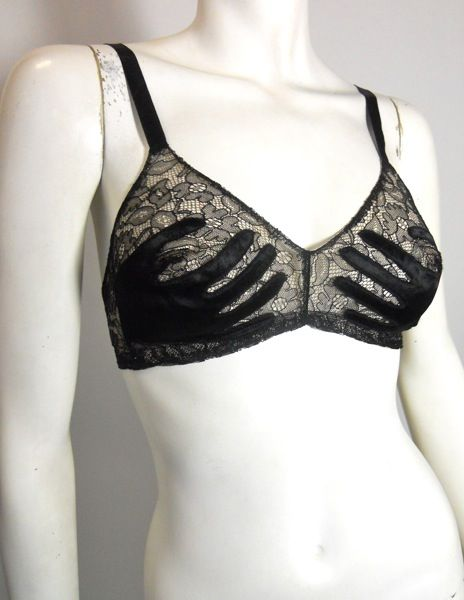 """Surrealist late 1930s to early 1940s Schiaparelli-esque black lace over nude mesh bra with black silk satin """"hands"""" on cups. Black silk straps, narrow elastic with single metal hook in back hooks into metal grommets on other side."""