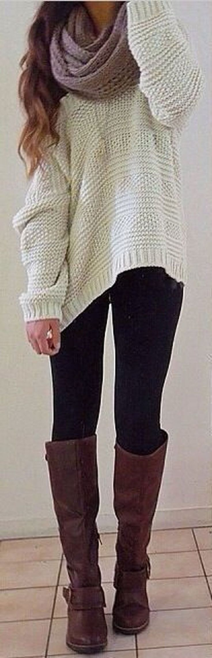 White or tan sweater with black leggings and brown boots.
