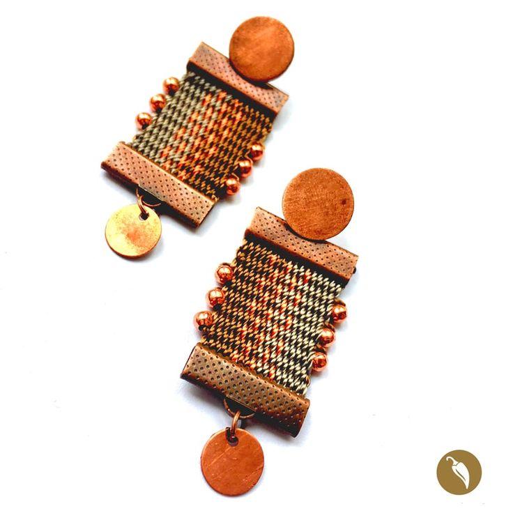 """: Arosdonde el protagonista absoluto es una pequeña pieza tejida a telar. Gabriela Casteránrescata estatécnica para honrar nuestros orígenes. De un tope metálico se suspende la pieza a telar.El brillo del metal se contrapone a la calidez de las fibras de tonos terracota en los que sedistingue un diseño en el centro. Estos aros son parte de la colecciónNahuenque alude al fonema Newen que significa """"Energía""""enMapudungún. El arte textil mapuche data de tiempos precolombinos y…"""