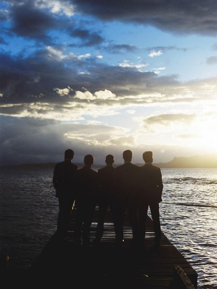 Wedding Photo of Silhouette of Groomsmen standing on a dock looking out into the sunset. This beautiful location is Rockwater Secret Cove Resort on the Sunshine Coast in BC, Canada.